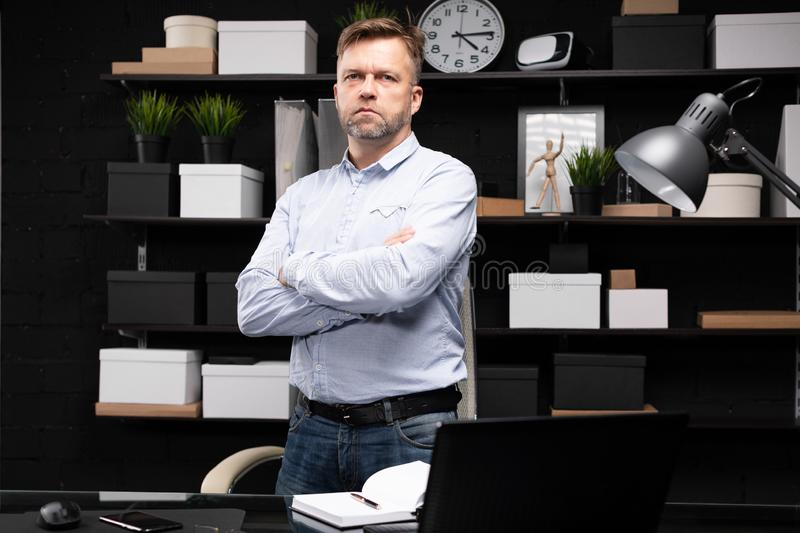 Young man stands near the computer table and folded his hands on his chest. Respectable man stands near computer Desk in stylish office and crossed his arms on stock image