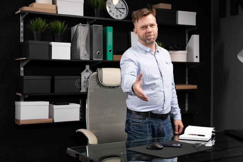 Young man stands near computer table and stretches his hand forward. Respectable man stands near computer Desk in stylish office and stretches his hand forward royalty free stock photo