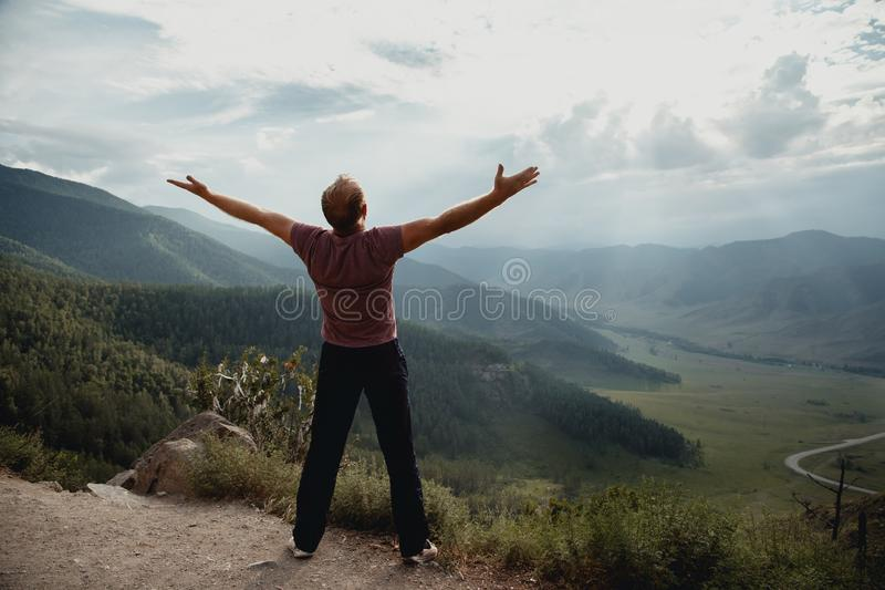 The young man stands on a rock and looks at the valley. Trekking in the mountains stock photo