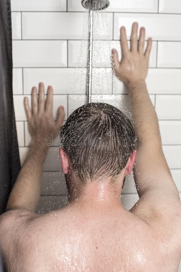 A young man stands in the shower under running water and leans h royalty free stock images