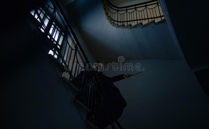 Young man stands on stairs in image of black magician with magic wand royalty free stock photography