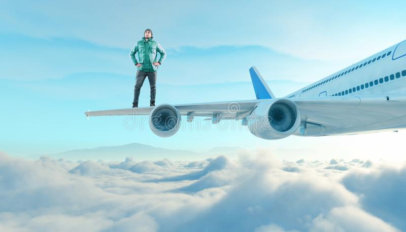 The young man stands on the wing of a plane. Above the clouds stock photos