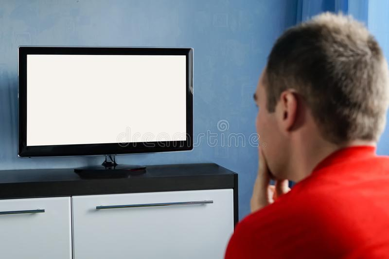 The young man stares at the TV. Blank screen white screen stock photo