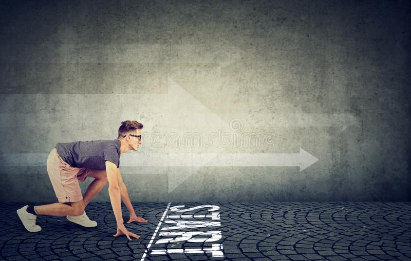 Young man in the starting position ready to run. Young determined man in the starting position ready to run stock photos
