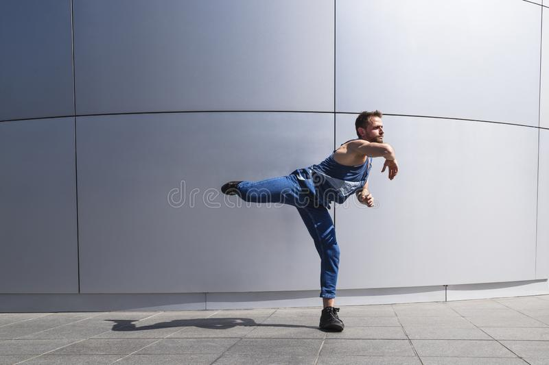 Young man street dancer dancing on wall background stock photo
