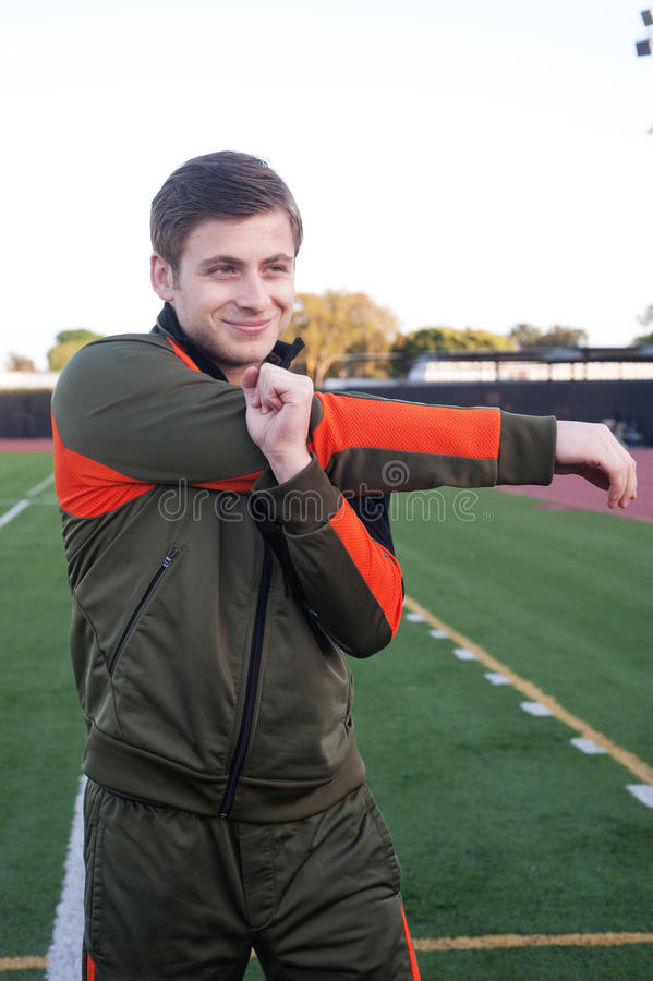 Young man stretching on athletic field stock image