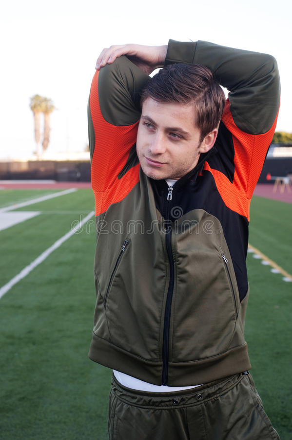 Young man stretching on athletic field royalty free stock photography