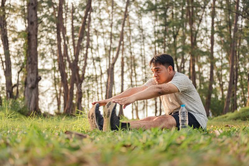 Young man stretching body before running at the park and sunset time stock photography