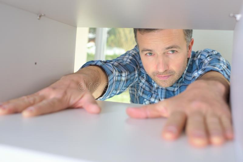 Young man stretching hands into cardboard box. Young man is stretching hands into cardboard box stock image