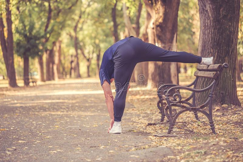 Young sporty man stretching his legs in the park royalty free stock image