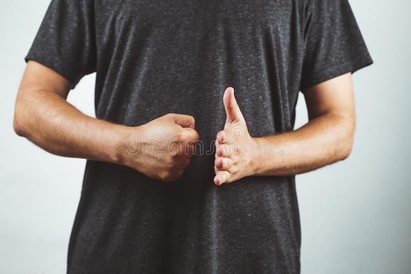 Young man striking a fist against the palm of the other hand - Fist against the palm. Violence, stop, woman, women, aggression, punch, attack, background stock photos