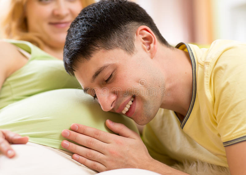 Young man strokes tummy of his pregnant woman. Young men strokes tummy of his pregnant woman. Careful husband loving his pregnant wife stock image