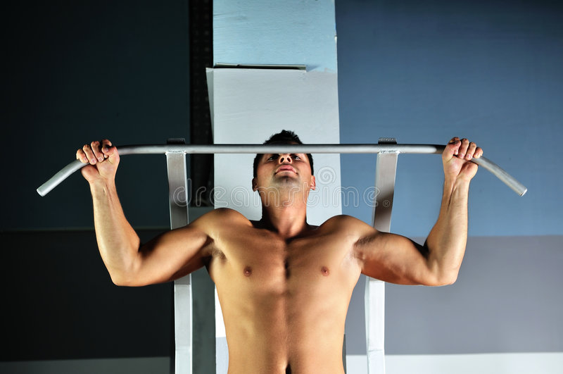 Young Man With Strong Arms Working Out In Gym Stock Photos