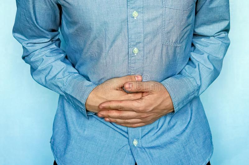 Young man with strong stomach pain stock images
