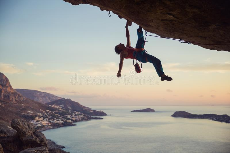Young man struggling to climb challenging route on cliff. Young man struggling to climb ledge on cliff, view of coast below stock images