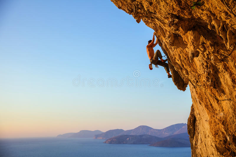 Young man struggling to climb challenging route on cliff at suns. Et, view of coast below royalty free stock photos