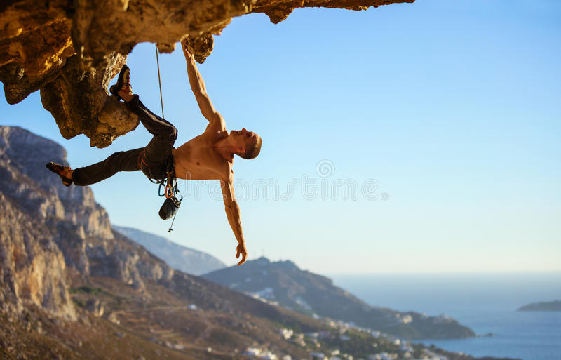 Young man struggling to climb ledge on cliff. View of coast below stock image