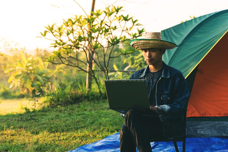 Young man using laptop during camping in the morning royalty free stock photography