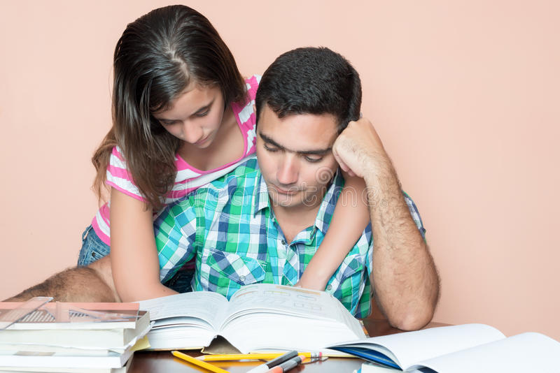Young man studying with his daughter hugging him royalty free stock photography