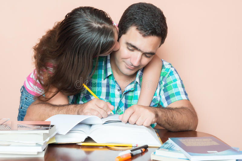 Young man studying with his daughter kissing him stock photo
