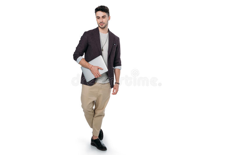 Young man in stylish clothes holding laptop and looking at camera. Isolated on white stock photos