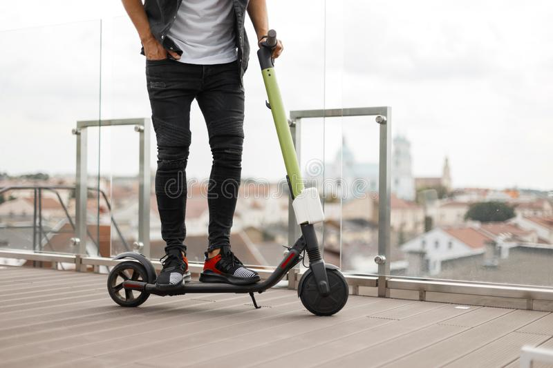 Young man in stylish jeans clothes in fashionable black sneakers is resting on an electric scooter. Urban guy stands. On a modern scooter on the background of royalty free stock photo