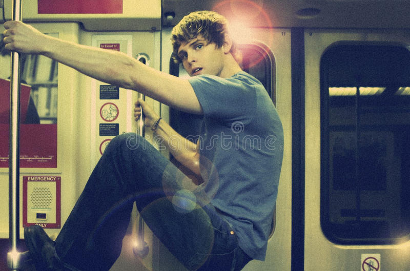 Young man on subway. Young man riding subway with overall vintage toning and gritty film grain for true retro look and feel stock images