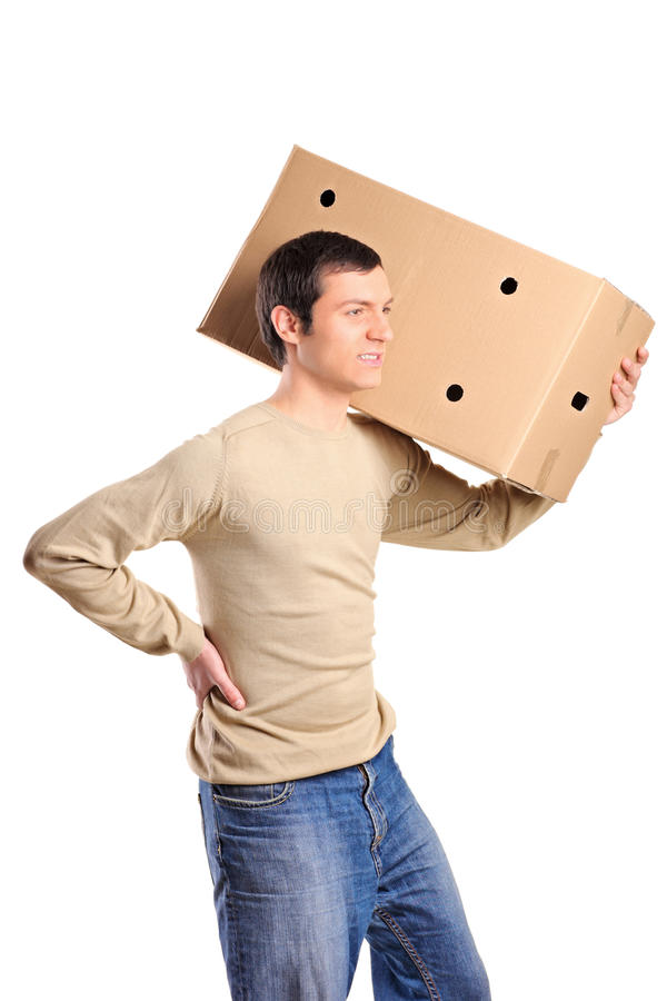 A young man suffering from back pain. While lifting a large box isolated on white background stock photography