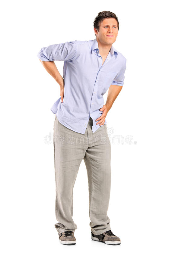 Young man suffering from a back pain. Full length portrait of a young man suffering from a back pain on white background royalty free stock photos