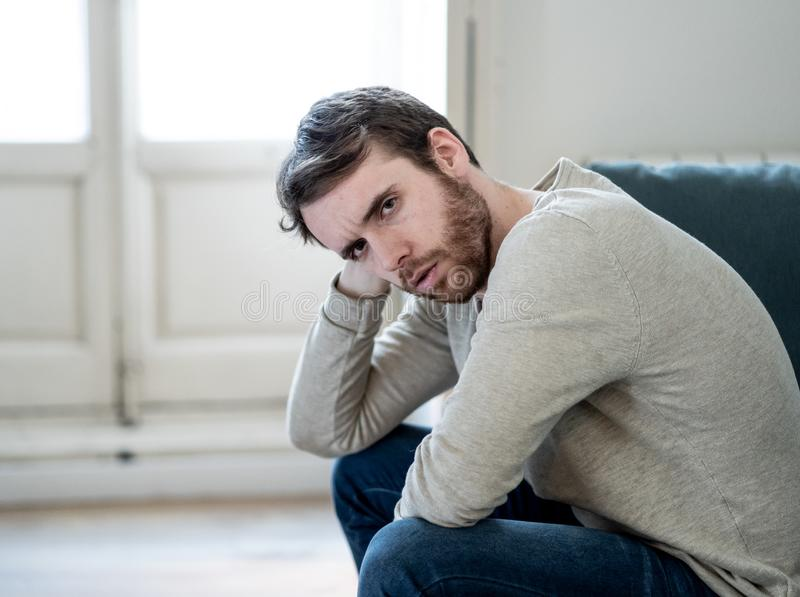 Young man suffering from depression hopeless and alone at home. Unhappy depressed caucasian male sitting and lying in living room couch feeling desperate a stock photo
