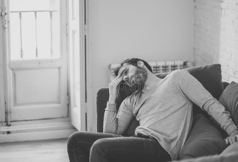 Young man suffering from depression hopeless and alone at home. Unhappy depressed caucasian male sitting and lying in living room couch feeling desperate a stock image
