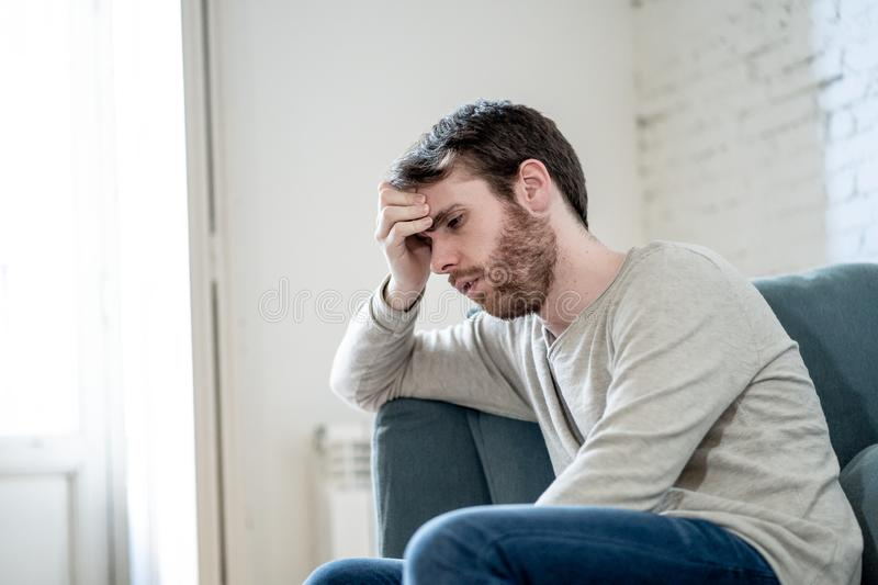 Young man suffering from depression hopeless and alone at home. Unhappy depressed caucasian male sitting and lying in living room couch feeling desperate a stock photos