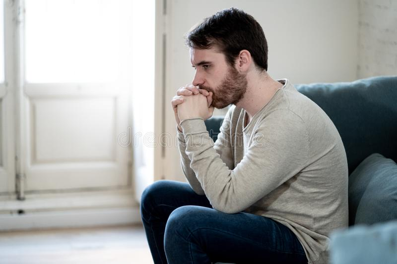Young man suffering from depression hopeless and alone at home. Unhappy depressed caucasian male sitting and lying in living room couch feeling desperate a royalty free stock images