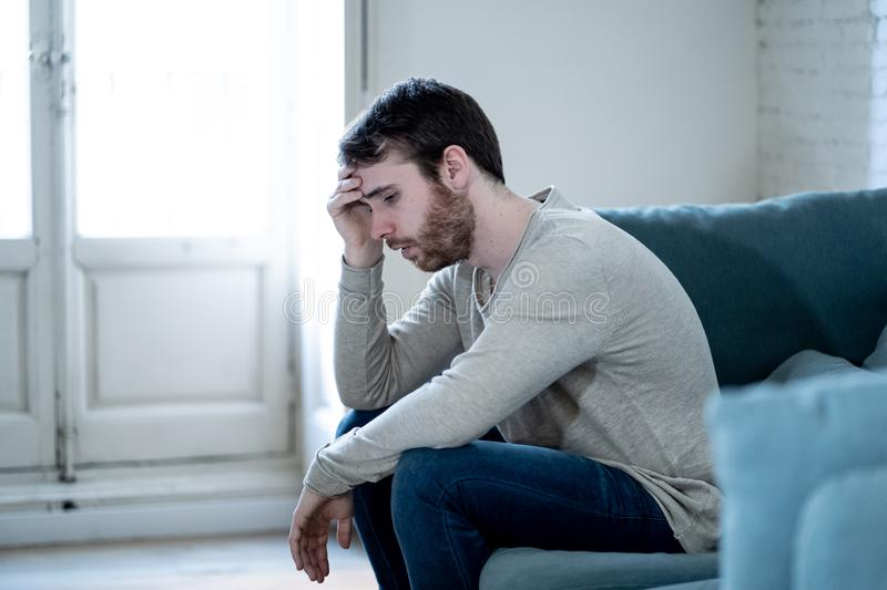 Young man suffering from depression hopeless and alone at home. Unhappy depressed caucasian male sitting and lying in living room couch feeling desperate a royalty free stock image