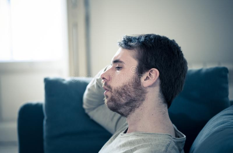 Young man suffering from depression hopeless and alone at home. Unhappy depressed caucasian male sitting and lying in living room couch feeling desperate a royalty free stock photo