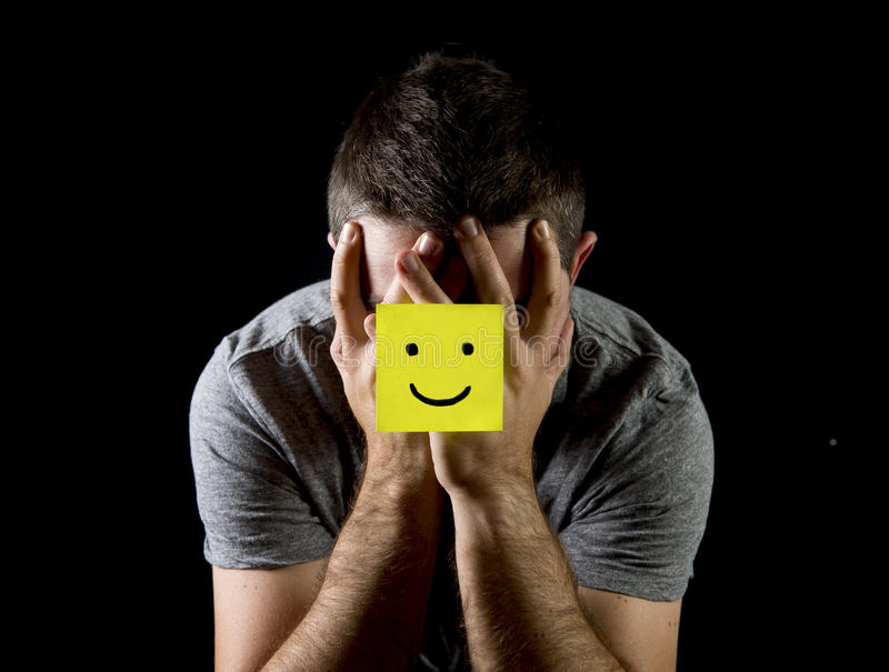 Young man suffering depression and stress alone with smiley face post it note royalty free stock photos