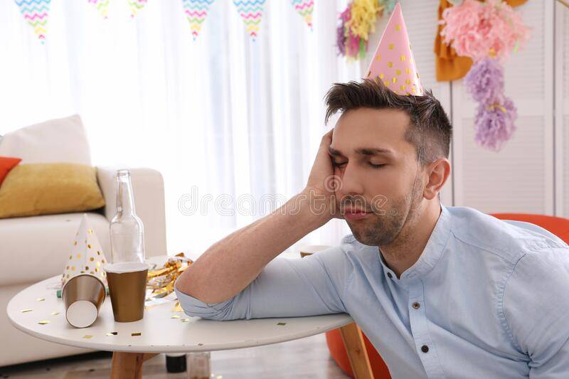 Young man suffering from hangover in room stock photo