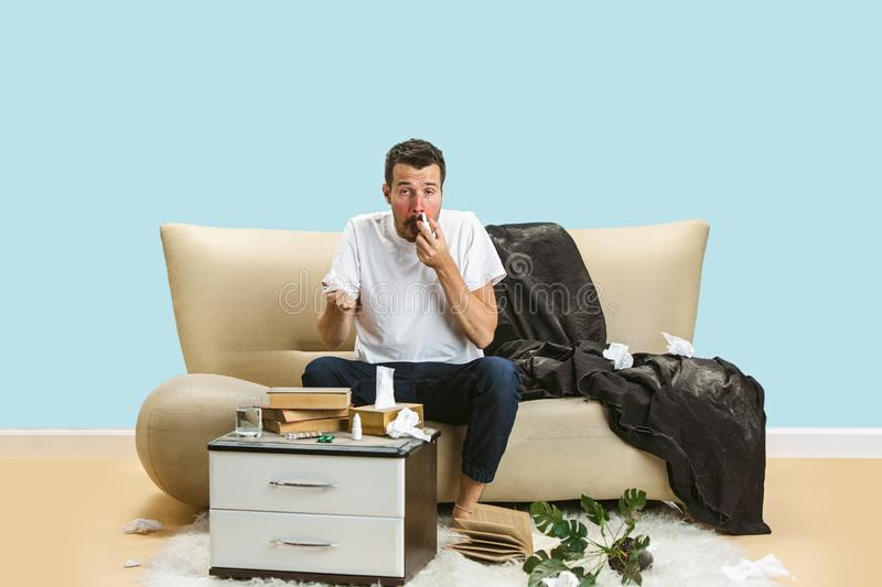 Young man suffering from hausehold dust or seasonal allergy. Sneezing in the napkin, sitting surrounded by used napkins on the floor. Taking nose spray royalty free stock photo