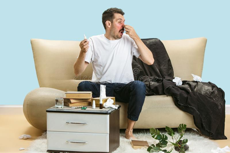 Young man suffering from hausehold dust or seasonal allergy. Sneezing in the napkin, sitting surrounded by used napkins on the floor. Taking nose spray stock photos