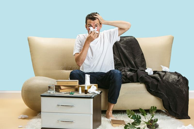Young man suffering from hausehold dust or seasonal allergy. Young man suffering from hausehold dust or seasonal allergy and headache. Sneezing in the napkin stock photos