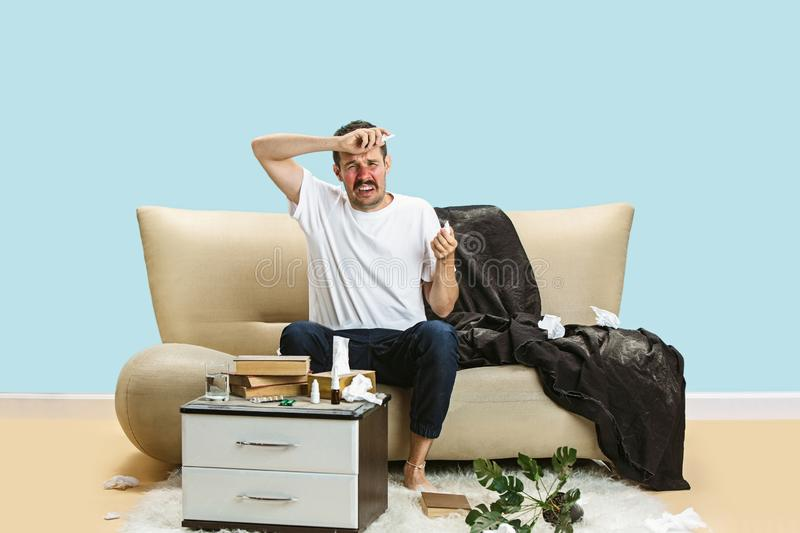 Young man suffering from hausehold dust or seasonal allergy. Young man suffering from hausehold dust or seasonal allergy and headache. Sneezing in the napkin royalty free stock image