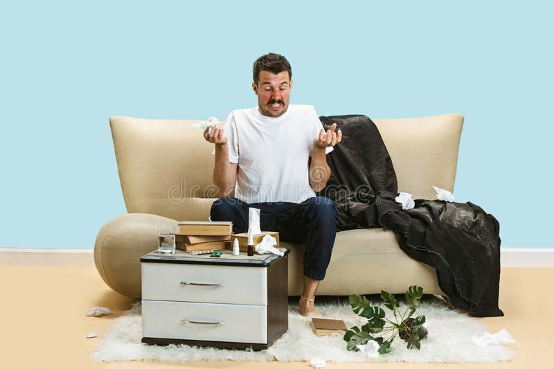 Young man suffering from hausehold dust or seasonal allergy. Sneezing in the napkin and sitting surrounded by used napkins on the floor and sofa. Taking stock photo