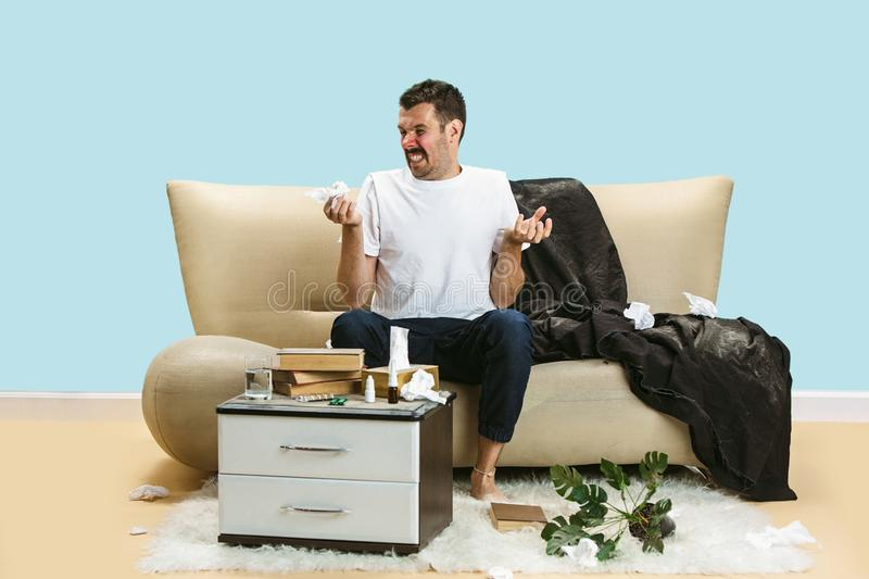 Young man suffering from hausehold dust or seasonal allergy. Sneezing in the napkin and sitting surrounded by used napkins on the floor and sofa. Taking stock photography