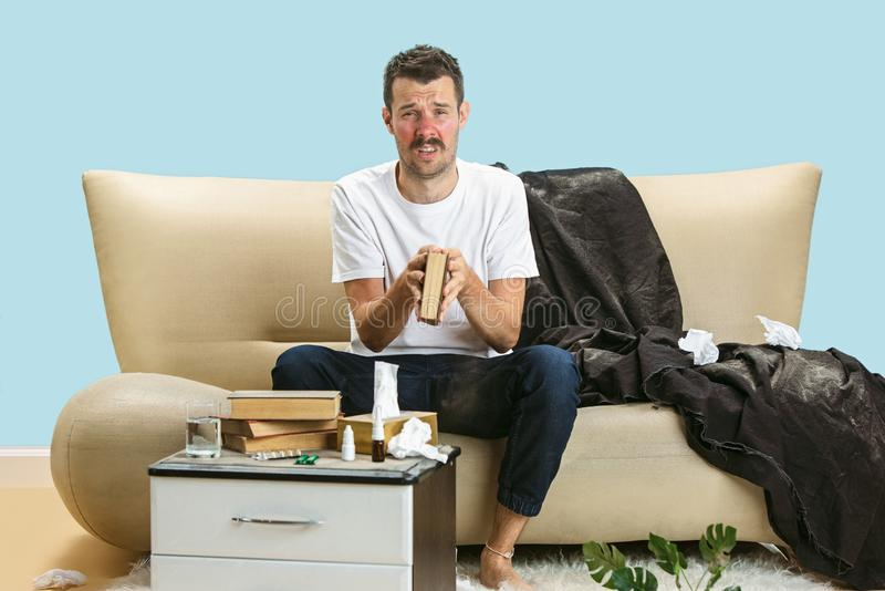 Young man suffering from hausehold dust or seasonal allergy. Sneezing in the napkin and sitting surrounded by used napkins on the floor and sofa. Taking stock images