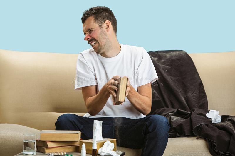 Young man suffering from hausehold dust or seasonal allergy. Sneezing in the napkin and sitting surrounded by used napkins on the floor and sofa. Taking royalty free stock photo