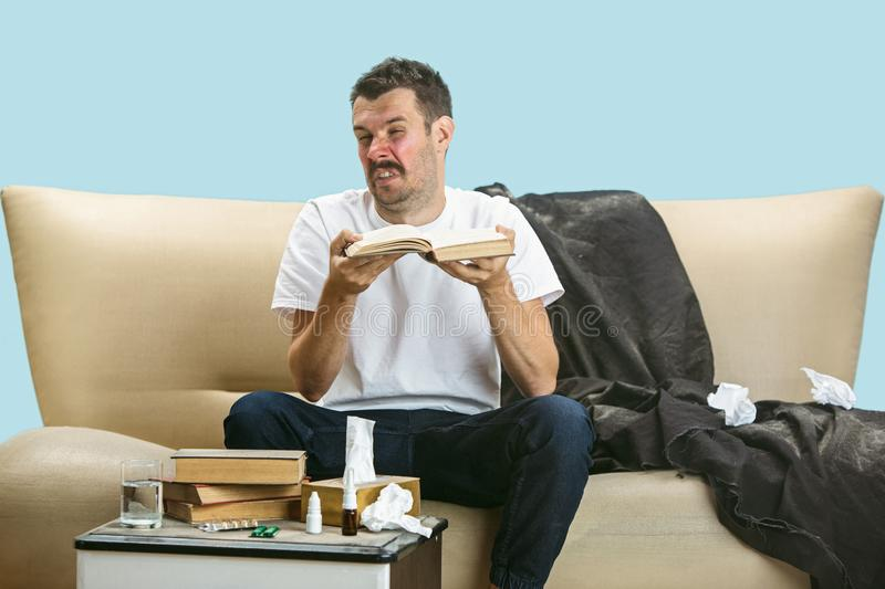Young man suffering from hausehold dust or seasonal allergy. Sneezing in the napkin and sitting surrounded by used napkins on the floor and sofa. Taking royalty free stock photos