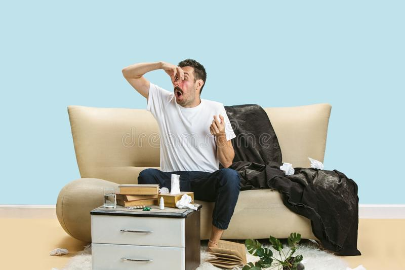 Young man suffering from hausehold dust or seasonal allergy. Sneezing in the napkin, sitting surrounded by used napkins on the floor. Taking nose spray royalty free stock photography