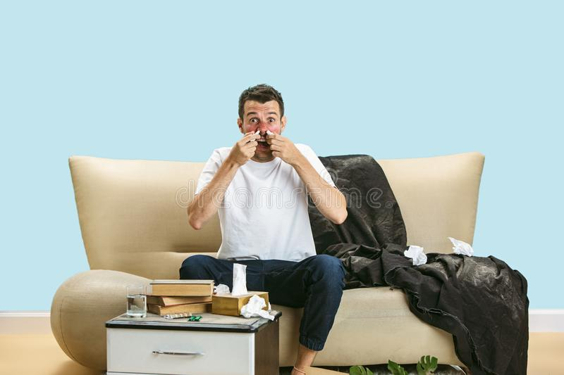 Young man suffering from hausehold dust or seasonal allergy. Sneezing in the napkin, sitting surrounded by used napkins on the floor. Taking nose spray stock images