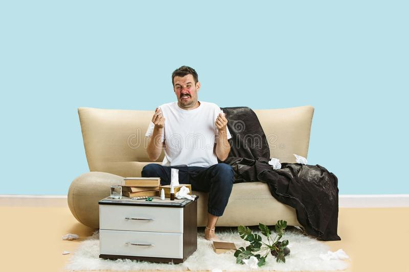Young man suffering from hausehold dust or seasonal allergy. Sneezing in the napkin, sitting surrounded by used napkins on the floor. Taking nose spray stock photography