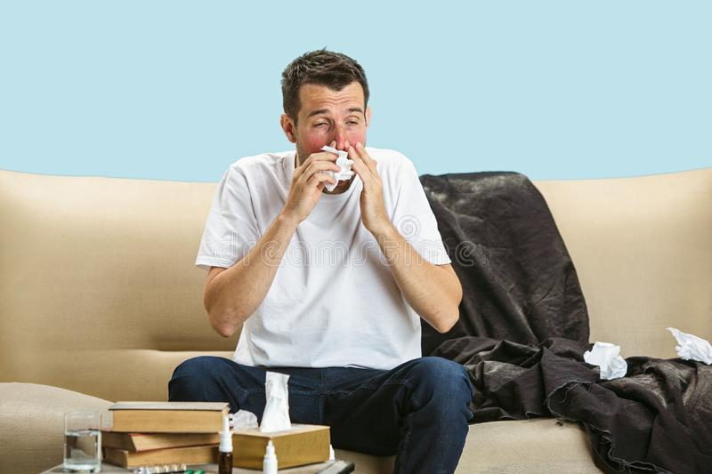 Young man suffering from hausehold dust or seasonal allergy. Sneezing in the napkin and sitting surrounded by used napkins on the floor and sofa. Taking stock photos